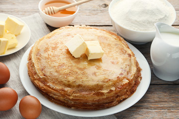Heap of pancakes in plate with butter on grey wooden table