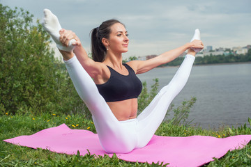 Woman holding legs apart doing exercises aerobics warming up with gymnastics for flexibility leg stretching workout outdoors.