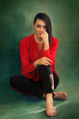 Beautiful attractive business fashion woman wearing red shirt and black pants, sitting and embracing her legs on floor, green background, barefoot, posing, relaxing, after work