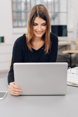 Young businesswoman smiling at her laptop