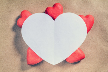 Big white heart with little red hearts on brown paper background. Valentine's day