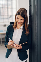 Young woman standing writing notes