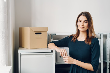 Relaxed businesswoman leaning on a cabinet