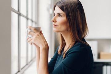 Woman holding a cup of coffee while daydreaming