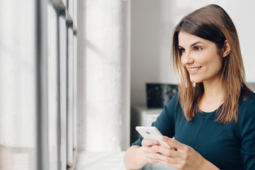 Young smiling woman with phone by window