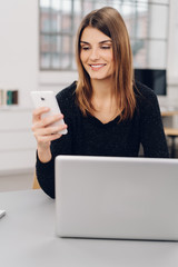 Young cheerful woman using mobile phone in office