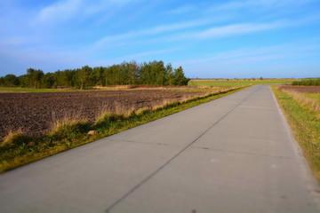 droga betonowa przez pola i lasy