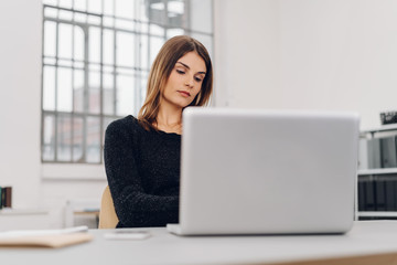Woman working on laptop at her desk in the office