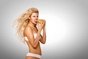 Eating burger / Beautiful pinup model eating a hamburger on grey background.