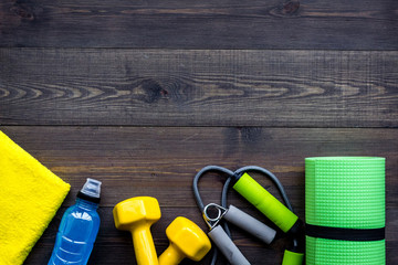 Fitness equipment. Jump rope, dumbbells, expander, mat, water on dark wooden background top view copyspace Wall mural