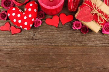 Valentines Day top border of hearts, gifts, flowers and decor against a rustic wood background with copy space.