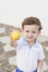 Child with a lemon in his hand
