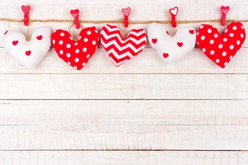 Valentines Day handmade, patterned cloth heart pillows hanging from a line. Top border against a rustic white wood background.