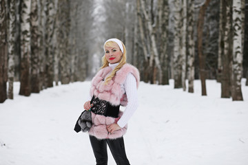 Blonde girl on a walk in a winter park
