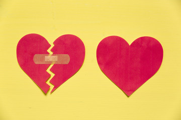 Broken paper heart with patch next to the whole paper heart on yellow background. Rebuild relationship concept