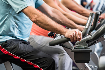 Group of people spinning at the gym on fitness bikes