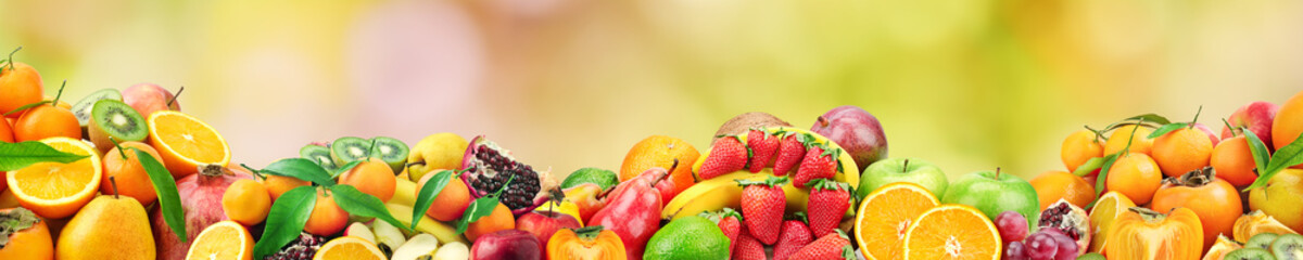 Wall Mural - Fresh healthy fruits on natural blurred multicolored background.