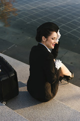 happy young woman stewardess in uniform sits in park in the sun