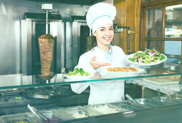 Positive brunette girl with kebab and vegetables