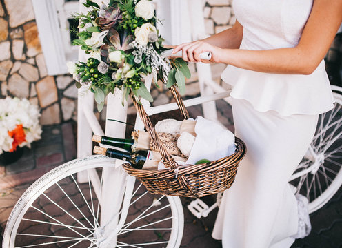 bride in a wedding dress near a white bicycle with a basket of baguette and wine and with a white and green wedding bouquet in Italian style