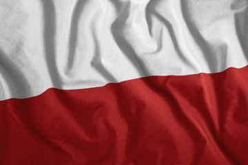 The Polish flag is flying in the wind. Colorful, national flag of Poland. Patriotism, a patriotic symbol.