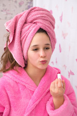 Funny young girl use lipstick for his face in the bathroom