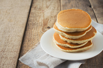 Pancakes day background, stack of homemade pancake over wooden table