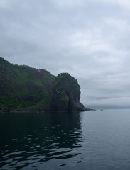 Rocky cliffs of the coastline of Shiretoko National Park hidden in a heavy layer of fog, Shiretoko National Park, Hokkkaido, Japan
