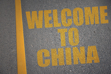 asphalt road with text welcome to china near yellow line.