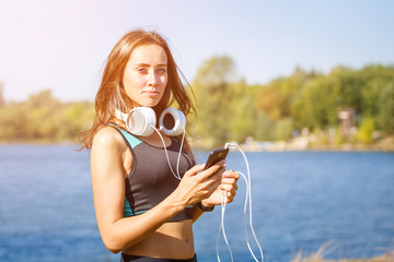 Young sporty woman using smartphone on training . Smiling girl with headphones enjoying outdoor workout at summer morning