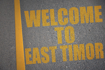 asphalt road with text welcome to east timor near yellow line.
