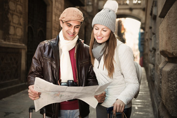 Man and woman with map and package looking attraction outdoors