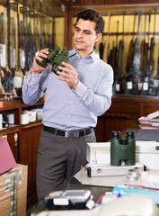 Serious man choosing new binocular for hunting in store with hunt equipment