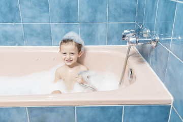 Smiling child playing in the bath