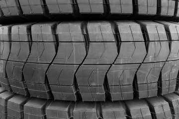 Stack of giant industrial size black rubber tires with tread patterns.