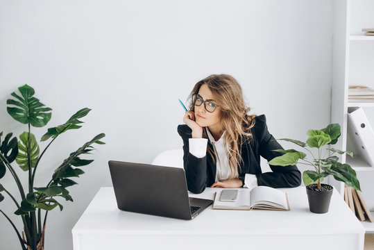 Serious business woman in a glasses and in suit, with a laptop sits at her workplace in a bright office and looks at the camera
