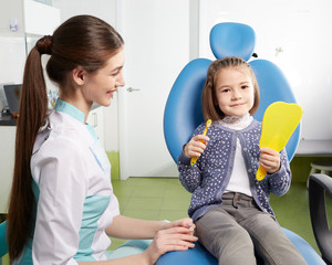 A little girl is sitting in a dental chair in a dentist's office with a toothbrush