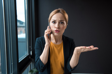 Portrait of surprised girl talking by phone while flourishing arm. Business and conversation concept