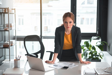 Portrait of serious businesswoman leaning on table. She looking at camera. Occupation and career concept