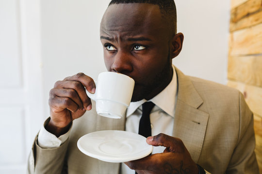 Young african businessman drinking coffee