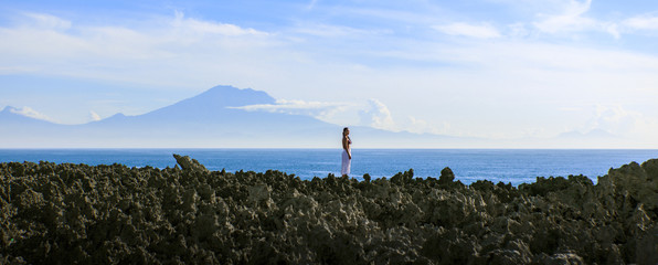 Asian woman standing on the volcanic cliff edge
