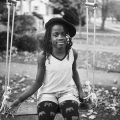 Stylish black girl with berret on a swing
