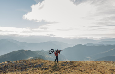 Young man carrying his mountain bike going up the mountain at the sunrise moment,
