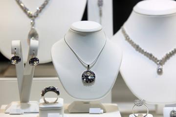 Obraz Srebrny naszyjnik, kolczyki i pierścień z diamentami na białych popiersiach w sklepie jubilerskim. - fototapety do salonu