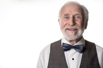 Portrait of kind elegant pensioner wearing bow tie. Copy space in left side. Isolated on background