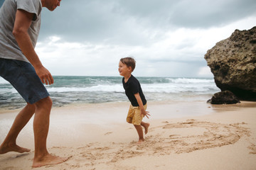 Fun loving dad playing with kids during vacation on beach