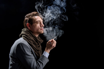 Depression. Side view profile of sad young stylish man is standing and enjoying cigarette. He is looking aside pensively while being in cloud of white smoke. Isolated with copy space in the right side