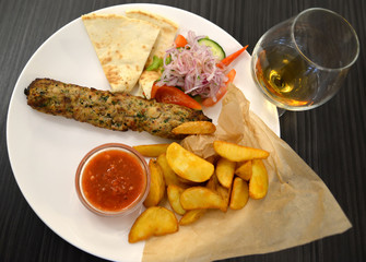 Kebab with a garnish from fried potatoes and fresh vegetables