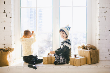 Children brother and sister of preschool age sit by window on a sunny Christmas day and play with gifts boxes wrapped in paper.They are dressed knitted warm woolen clothes and hat.Inside the house
