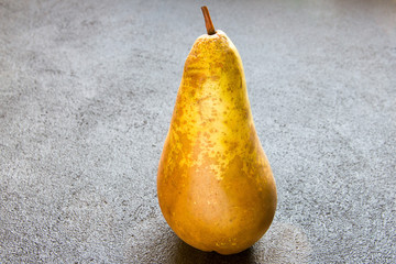 Juicy pear on a dark concrete background.